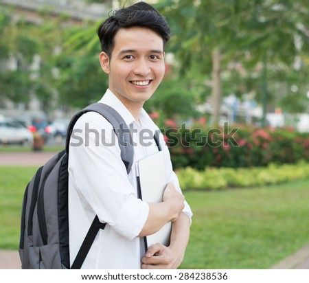 Asian student with laptop at the park - stock photo