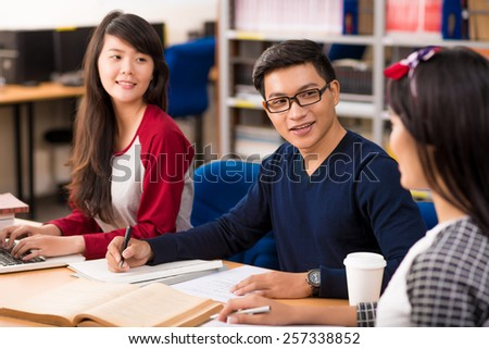 Asian students studying in a University library - stock photo
