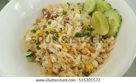 Asian-style fried rice with braised pork belly, sided with fresh vegetables and a lemon slice. Isolated on white plate.