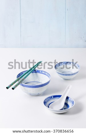 Asian style porcelan bowls and turquoise chopsticks over white kitchen table. Side view - stock photo