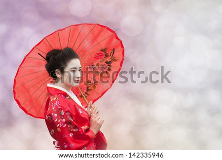 Asian style portrait of a woman with red umbrella on abstract background - stock photo