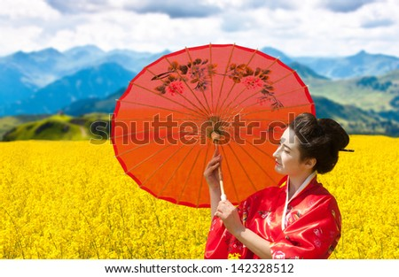 Asian style portrait of a woman with the red umbrella in the yellow flowering field, cloudy sky and mountains background - stock photo