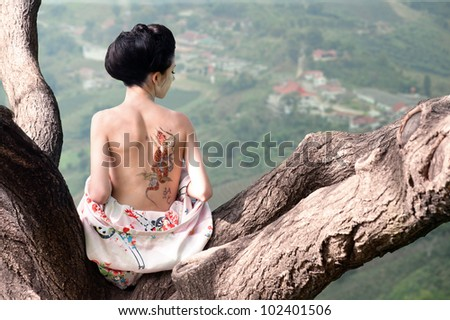 Asian style portrait of young woman sitting on the tree branch with snake tattoo on her back (original) - stock photo