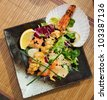 Asian style seafood dish on black plate - stock photo