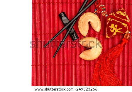 Asian style table place setting with chinese new years lucky charm, fortune cookies and chopsticks on red bamboo mat - stock photo