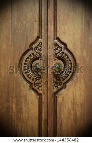 Asian-style wooden door with brass knockers. - stock photo