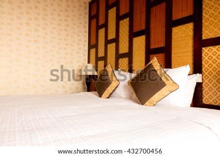 Asian stylish bedroom interior design with cushion pillows and table lamp - stock photo