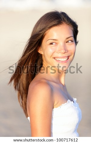 Asian summer woman happy. Fresh pretty brunette candid portrait on beach in sunset light. Beautiful young eurasian woman, mixed Chinese and Caucasian. - stock photo