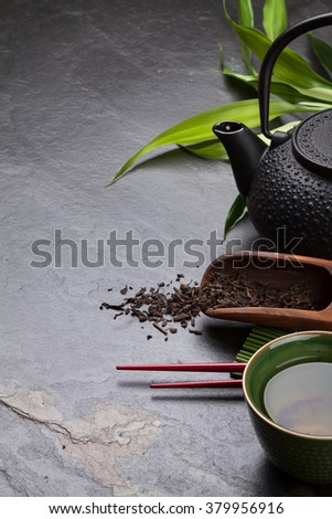Asian tea bowl and teapot over stone table. View with copy space