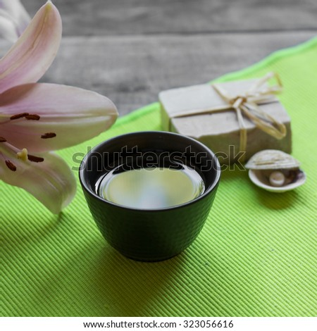 Asian tea cup and spa settings on wooden board, close up - stock photo
