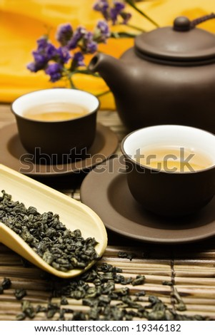 Asian tea set with dried green tea on a bamboo surface with a purple flower in the background. - stock photo