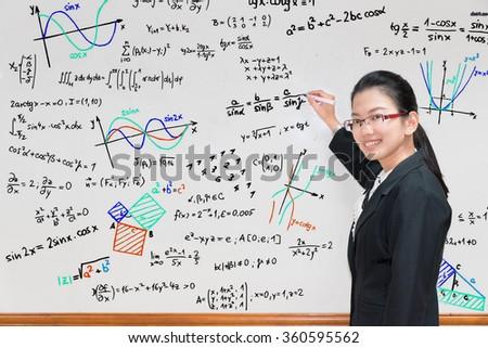 Asian teacher writing various high school maths formula on whiteboard - stock photo