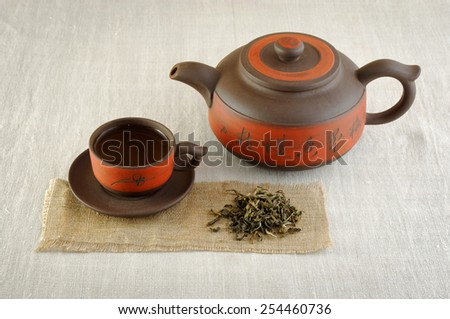 asian teapot and cup with tea on canvas with pile of dry tea near - stock photo