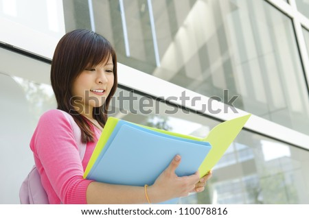 Asian teen student reading file folder outside school building - stock photo