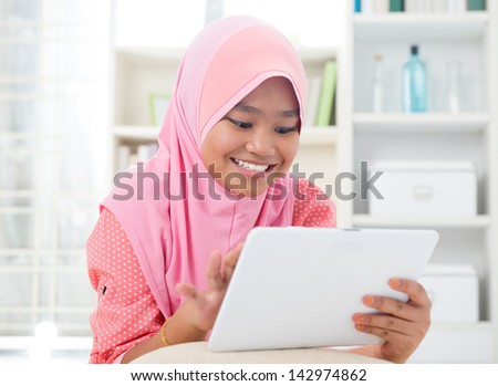 Asian teen using tablet pc computer. Southeast Asian teenager at home. Muslim teenage girl living lifestyle. - stock photo