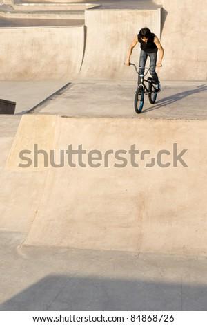 Asian Teenage boy on stunt bike ready to go. - stock photo