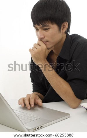 Asian teenage student sitting at desk using computer