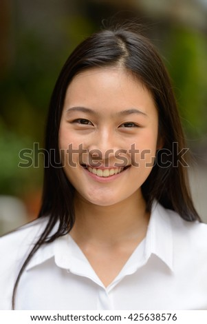 Asian teenage woman smiling outdoors