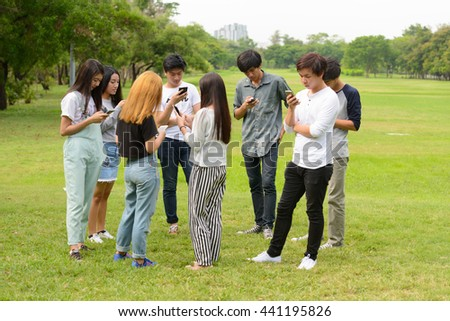 Asian teenager friends using phone in park