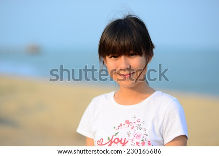 Asian teenager relaxing on the beach with nature light in the morning. - stock photo