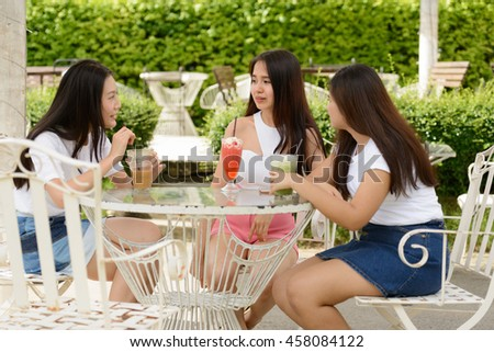 Asian teenagers friends sitting outdoors at restaurant - stock photo