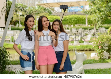 Asian teenagers friends taking picture outdoors - stock photo