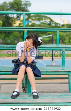 Asian Thai schoolgirl student in high school uniform education fashion is sitting on a metal stand and showing annoying sulk facial expression. She kept something in mind and not in good mood.  - stock photo