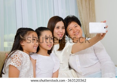 Asian three generations family taking photo of themselves using handphone - stock photo