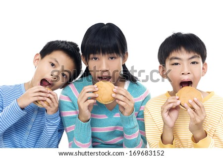 Asian three young friends eating hamburgers on white background - stock photo