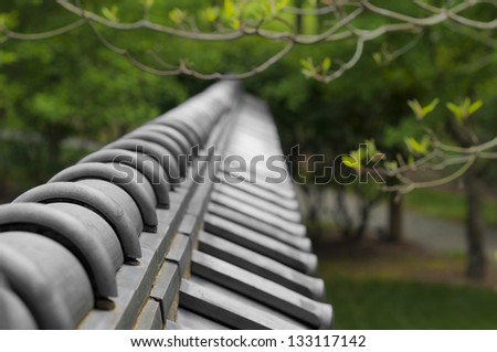 Asian tiled wall around a green garden - stock photo