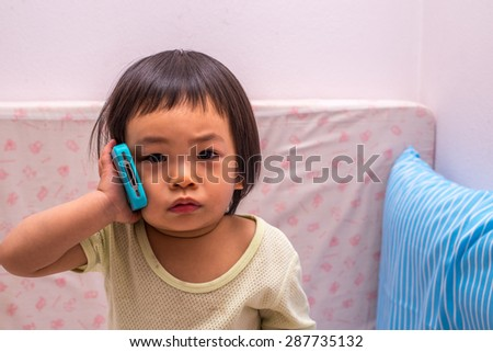 Asian toddler girl with cell phone - stock photo
