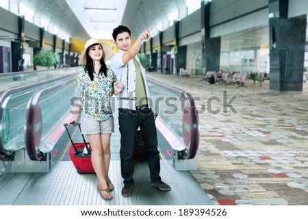 Asian tourist walking on escalator at airport - stock photo