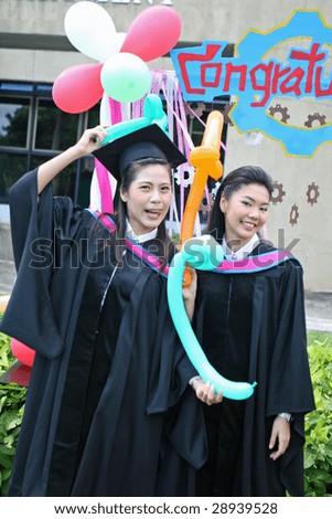 Asian university graduates celebrate their success. - stock photo