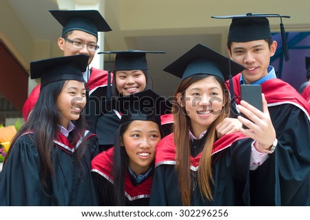 Asian university graduates taking photo with handphone