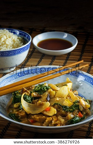 Asian vegetable dish with chopsticks on a bamboo mat, rice and soy sauce, background fades to dark for copy space, vertical, selected focus and narrow depth of field - stock photo