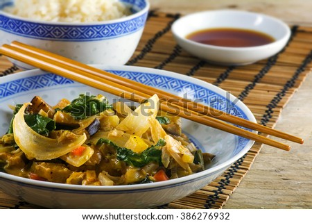 Asian vegetable onion dish with chopsticks on a bamboo mat and a rustic wooden table, rice and soy sauce blurred  in the background, close up with selected focus and narrow depth of field - stock photo