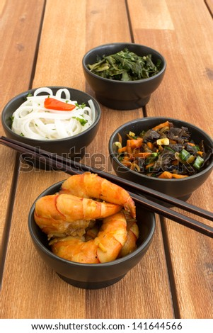 Asian vegetarian food composed with four black bowls with shrimps, rice noodles, kale (green cabbage), fried vegetables and chinese chopsticks. Composition on a old styled wooden table. - stock photo