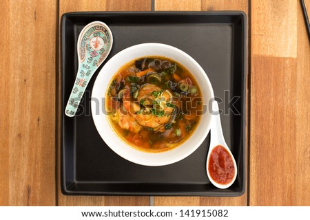 Asian vegetarian soup with shrimps and spicy sauce composed with two ceramic spoons on a square black plate. Composition on a old styled wooden table. - stock photo