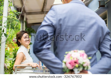 Asian wedding ,hide flower for surprise to his girlfriend. - stock photo