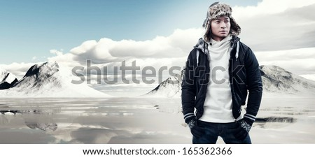 Asian winter fashion man in snow mountain landscape. Wearing black jacket with furry hat and gloves. - stock photo
