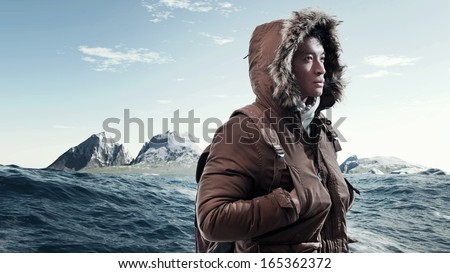 Asian winter sport fashion man with backpack in arctic mountain landscape. Wearing brown jacket with fur hoody and white gloves. - stock photo