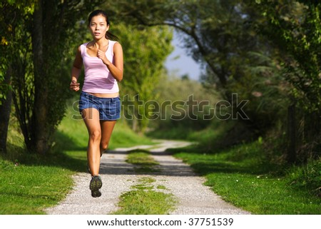 Asian woman active in forest. running. Girl running at great speed. Freeze action image on beautiful forest path. Beautiful female model. - stock photo
