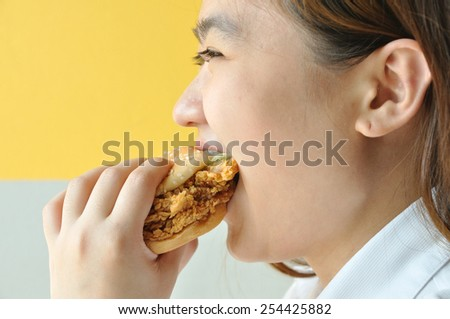 Asian woman age 28 years old in uniform eating chicken burger, junk food.