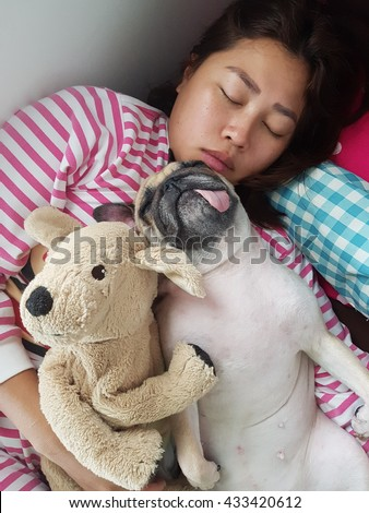 Asian Woman and her ugly pug dog sleep in the bed and hug in arms - stock photo