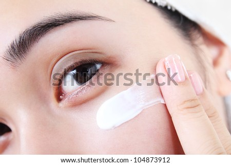 Asian woman applying facial lotion or moisturizer on her face.Close up. - stock photo