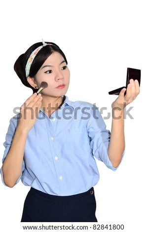 Asian woman applying make up on white background - stock photo