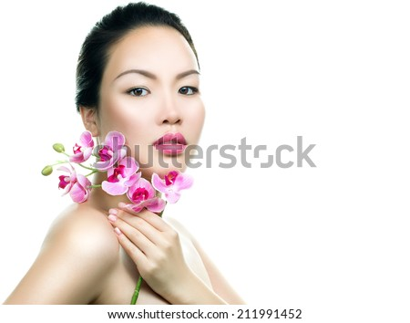 Asian woman beauty face closeup portrait. Beautiful attractive mixed race Chinese Asian / Caucasian female model with perfect skin, manicure and day make up, holding orchid flower isolated  - stock photo