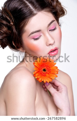 Asian woman beauty face closeup portrait with orange herbera. Beautiful attractive mixed race Chinese Asian / Caucasian female model with perfect skin and pink make up - stock photo