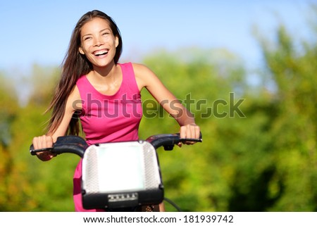 Asian woman biking in city park on bicycle. Happy girl on bike cycling outdoors in summer smiling of joy during outdoor activity. - stock photo
