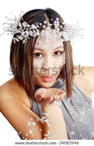 Asian woman blowing snow from her hands
